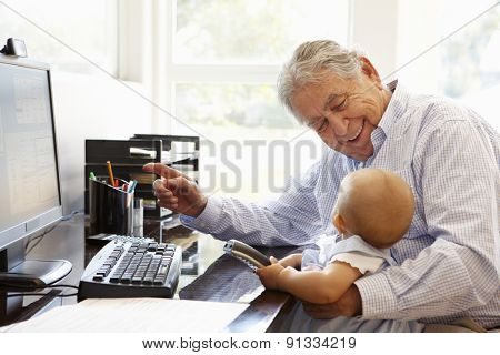 Senior Hispanic man with computer and baby