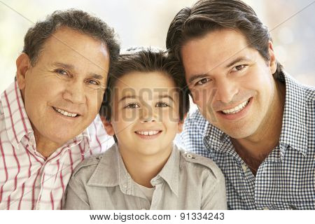 Portrait Of Hispanic Grandfather, Adult Father And Son Relaxing At Home