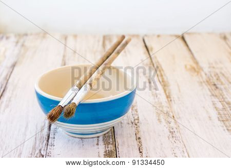 Paint Brushes And Ceramic Bowl On Wooden Background