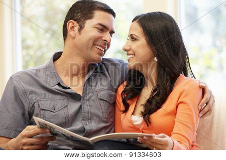 Hispanic couple at home reading magazine