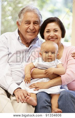 Hispanic grandparents at home with grandchild