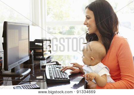 Hispanic mother with baby working in home office