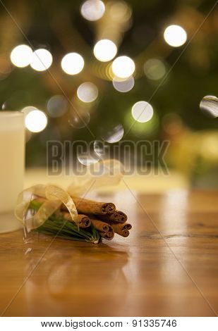 Cinnamon On A Wooden Table Infront Of A Christmas Tree