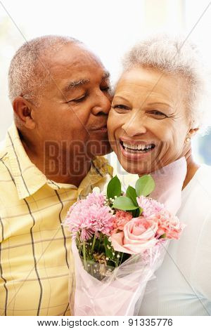 Senior man giving flowers to wife