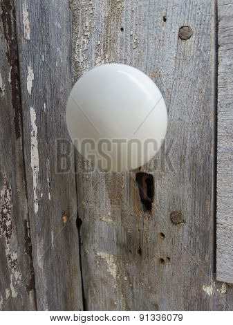 Smooth White Doorknob on Rough Wood