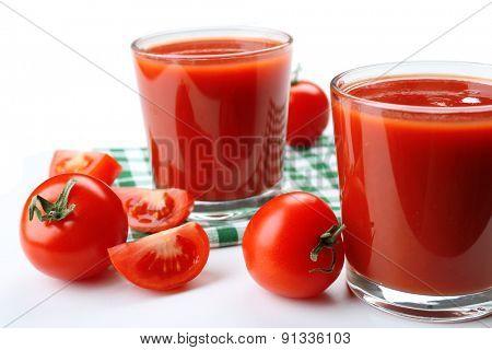 Glasses of fresh tomato juice on checkered napkin, isolated on white