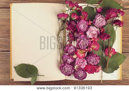 Dried roses with book, top view