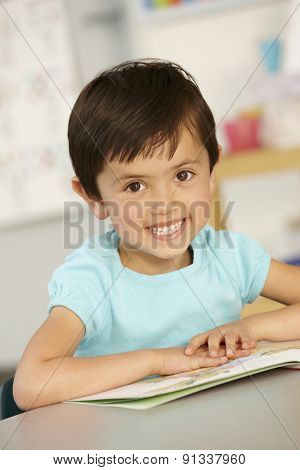 Elementary Age Schoolgirl Reading Book In Class