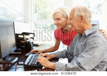 Senior man and daughter using computer at home