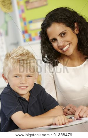 Elementary Age Schoolboy Reading Book In Class With Teacher