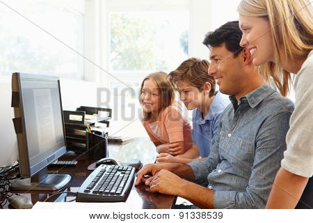 Family with computer in home office