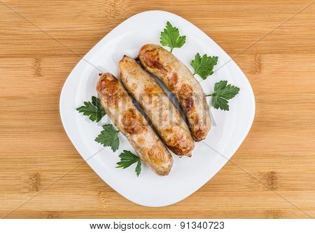 Three Fried Pork Sausages With Parsley In Plate On Table