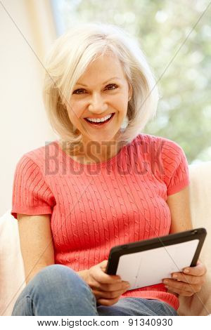 Mid age woman using tablet at home