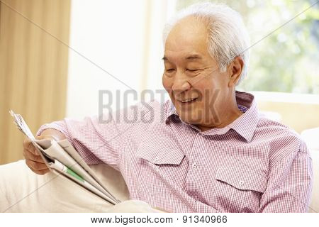 Senior Asian man reading newspaper