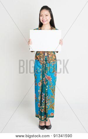 Full body portrait of Southeast Asian girl in batik dress hands holding white blank placard, standing on plain background.