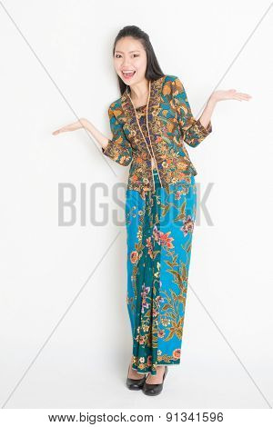 Full body portrait of cheerful Southeast Asian woman in batik dress hands showing something, standing on plain background.