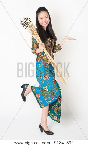 Full body portrait of Southeast Asian woman in batik dress hand holding bamboo oil lamp showing something standing on plain background.