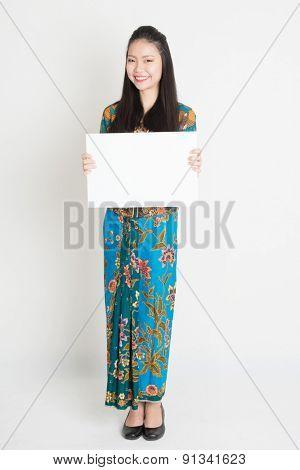 Full body portrait of Southeast Asian girl in batik dress hands holding white blank board, standing on plain background.