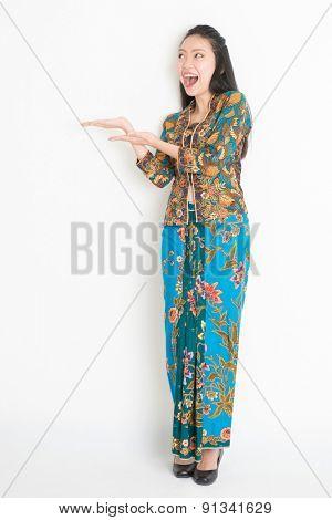 Full body portrait of excited Southeast Asian girl in batik dress hand holding something, standing on plain background.