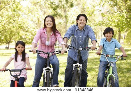 Asian family riding bikes in park