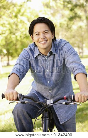 Asian man riding bike in park
