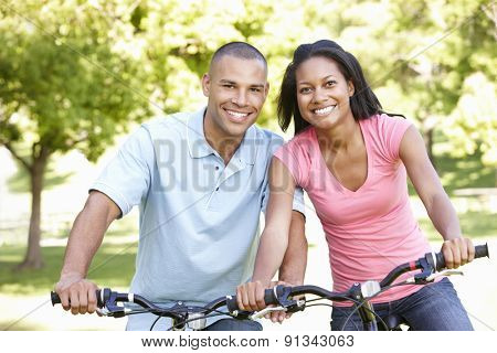 Young African American Couple Cycling In Park