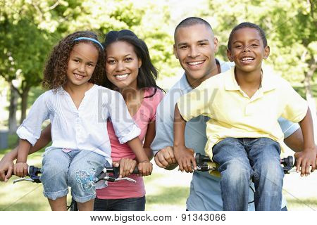 Young African American Family Cycling In Park