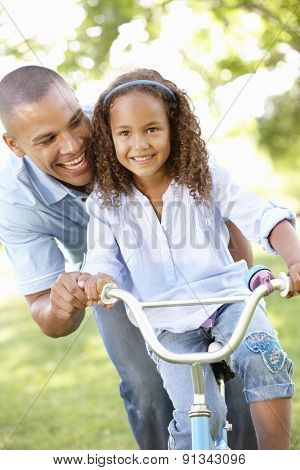 Father Teaching Daughter To Ride Bike In Park