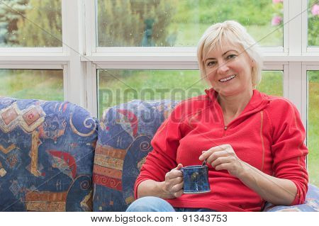Smiling Blonde Middle-aged Woman Is Relaxing On A Sofa