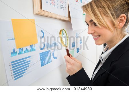 Businesswoman Examining Graph With Magnifying Glass