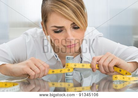 Businesswoman With Measuring Tape And Banknote