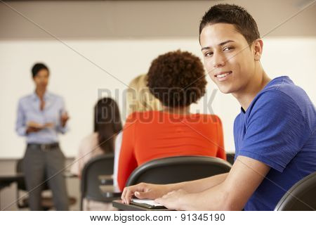 Teenage Hispanic boy in class smiling to camera