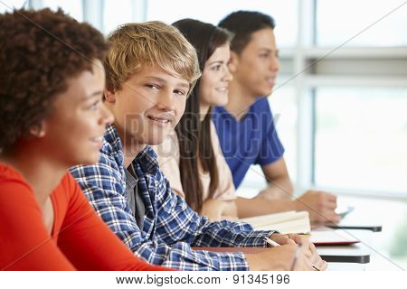 Multi racial teenage pupils in class, one smiling to camera