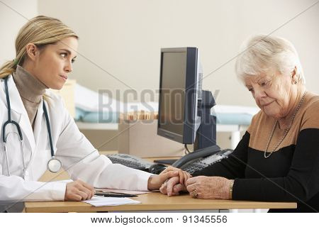 Doctor reassuring senior woman patient
