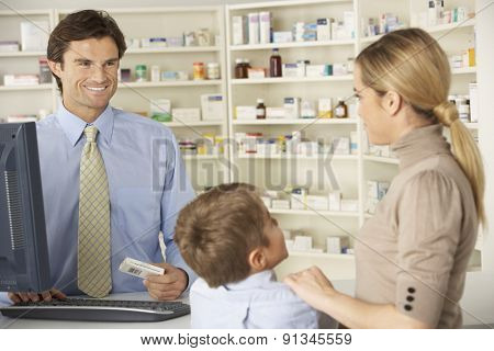 Pharmacist in pharmacy with mother and child