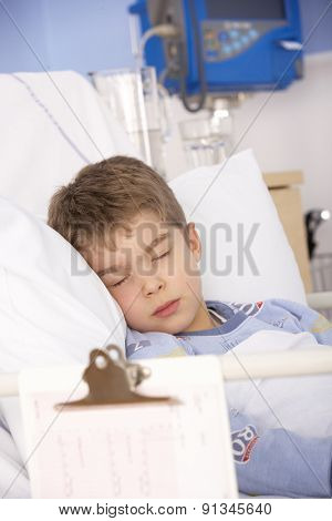 Young boy asleep in hospital bed