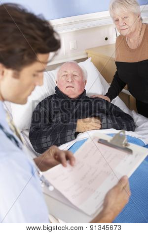 Doctor talking to senior couple in hospital