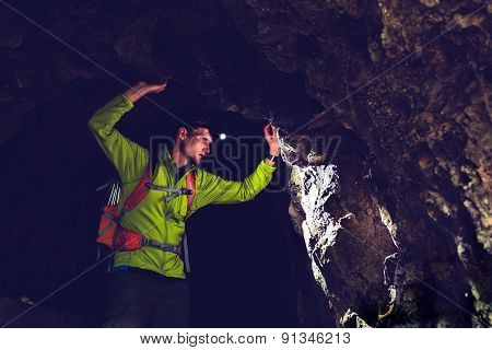 Man Exploring Underground Dark Cave Tunnel