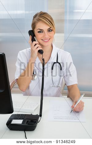 Young Female Doctor Talking On Telephone