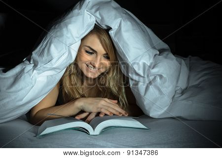Woman Under Bedding Reading Book