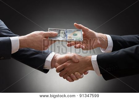 Businessmen Shaking Hands And Receiving Money