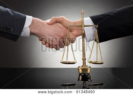 Businessman Shaking Hands In Front Of Scale