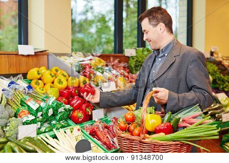 Smiling man buying frssh red pepper and other vegetables in a supermarket