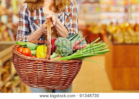 Woman carrying shopping basket full of vegetables in a supermarket