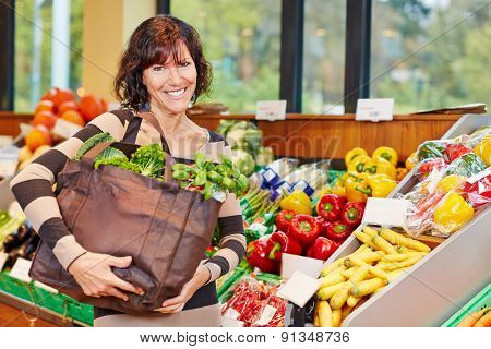 Smiling elderly woman with bag full of fresh vegetables in a supermarket