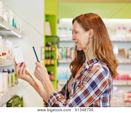 Elderly woman scanning barcode of cosmetics with smartophone in a drugstore