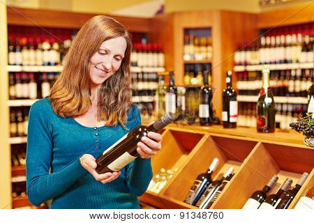 Elderly smiling woman buying bottle of red wine in a supermarket