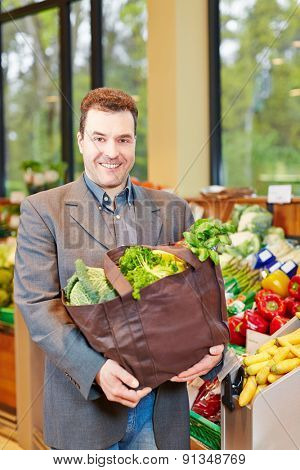 Smiling businessman buying fresh vegetables in a supermarket