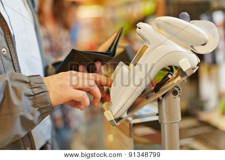 Man typing his PIN password at supermarket checkout in card reader
