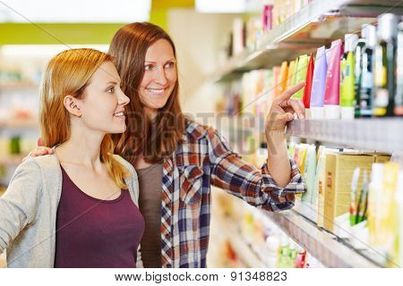 Mother giving her daughter shopping advice in a drugstore